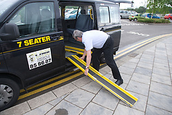 Taxi driver putting a disabled ramp on his taxi,