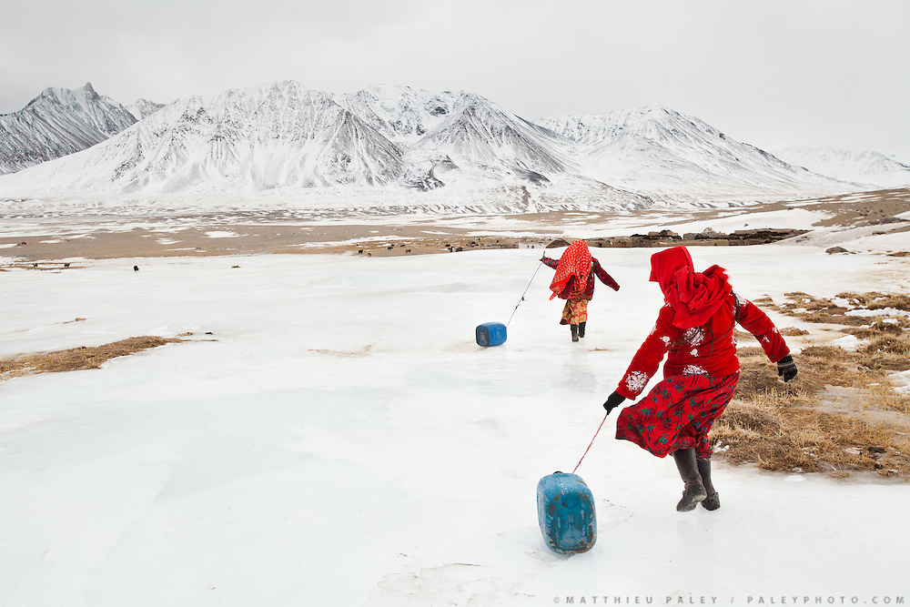 Kyrgyz girls slide large plastic jerry cans back to their family's camp after hacking a hole in the frozen river to fetch water. Men handle herding and trading; much of the hard labor of daily life falls to the women...