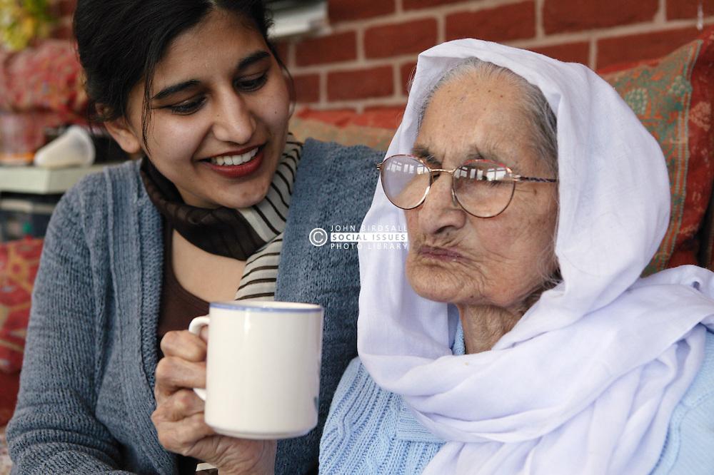Granddaughter sitting with her Sikh elderly grandmother drinking tea,