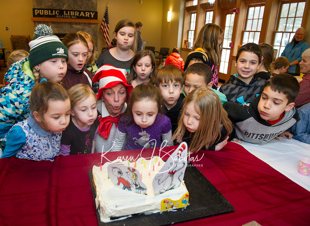 The Cat in the Hat has many helpers to blow out the candles on Dr. Seuss' birthday cake during the Read Across America event at the Gilford Library on Wednesday afternoon.  (Karen Bobotas/for the Laconia Daily Sun)