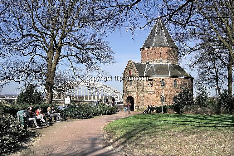 Nederland, Nijmegen, 12-3-2017Mensen genieten van de zon, en het uitzicht op de waal en de waalbrug vanaf het valkhof, valkhofpark . Het is een stadspark met de resten van de burcht, palz, van Karel de Grote . De Karolingische kapel deel uitmakend van de verdwenen palz Foto: Flip Franssen