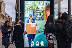Edinburgh, Scotland, UK. 21 October 2020. First Minister Nicola Sturgeon announces that bars and restaurants in Central Belt of Scotland to remain closed. Pictured; members of the public walk past NHS Covid-19 advice billboards on Princes Street. Iain Masterton/Alamy Live News