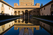 The Court of the Myrtles is reflected in a large pool, with a water fountain in the foreground, in the Casa Real complex, La Alhambra, Granada, Andalusia, Spain.