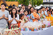 13 APRIL 2013 - BANGKOK, THAILAND:  People pray on the plaza in front of Bangkok City Hall during a merit making ceremony on Songkran. Songkran is the traditional Thai New Year's Festival. It is held April 13-16. Many Thais mark the holiday by going to temples and making merit by giving extra alms to monks or offering extra prayers. They also mark Songkran with joyous water fights. Songkran has been a national holiday since 1940, when Thailand moved the first day of the year to January 1.   PHOTO BY JACK KURTZ