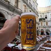 Male hand holding Efes beer glass in Cicek Pasaji, Istanbul, Turkey