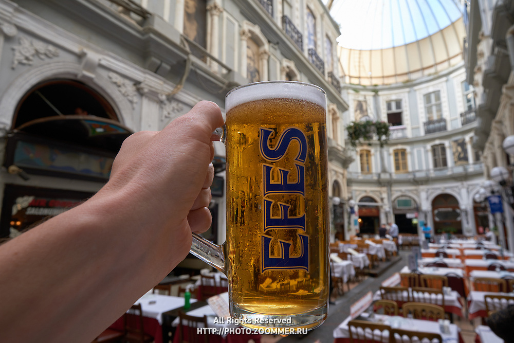 Male hand holding Efes beer glass in Cicek Pasaji, Istanbul, Turkey