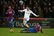 Roque Messa of Swansea city jumps a tackle from Jeffrey Schlupp of Crystal Palace. Premier league match, Swansea city v Crystal Palace at the Liberty Stadium in Swansea, South Wales on Saturday 23rd December 2017.<br /> pic by  Andrew Orchard, Andrew Orchard sports photography.