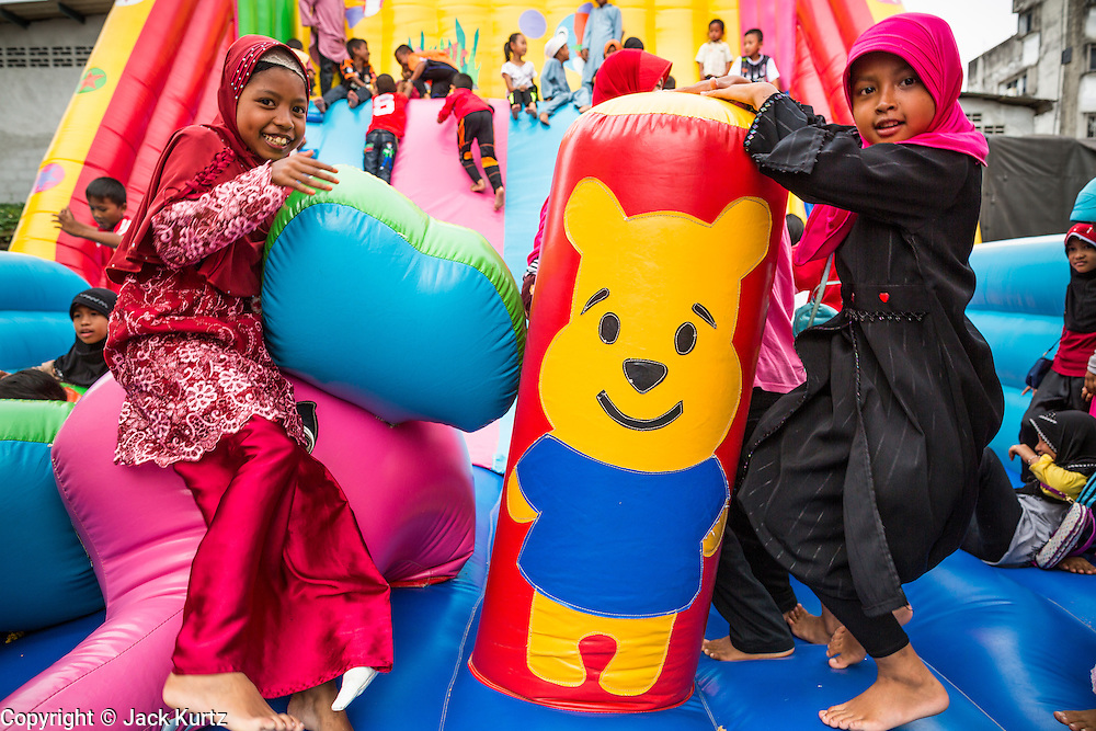 """07 JULY 2013 - NARATHIWAT, NARATHIWAT, THAILAND:   Thai Muslim children play in a """"bouncy house"""" set up by Royal Thai Marines Sunday. Royal Thai Marines in Narathiwat province held a special ceremony Sunday in advance of Ramadan. They presented widows, orphans and indigent people with extra rice and food as a part of the Thai government's outreach to resolve the Muslim insurgency that has wracked southern Thailand since 2004. The Holy Month of Ramadan starts on about July 9 this year. Muslims are expected to fast from dawn to dusk, engage in extra prayers, recitation of the Quran and perform extra acts of charity during Ramadan. It is the holiest month of the year for Muslims.  PHOTO BY JACK KURTZ"""
