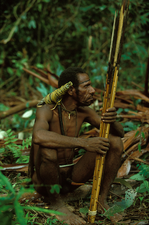 A Kombai man with stone axe and bow and arrows in Papua, Indonesia. September 2000. The Kombai are a so-called treehouse people who build their homes high up in the trees.