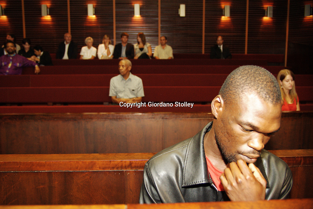PIETERMARITZBURG - 5 February 2007 - Fethe Nkwanyana, 23, avoids looking at the camera in the Pietermaritzburg High Court where he was sentenced to 25 years imprisonment for his part in the murder of famed Anglo-Zulu War historian David Rattray. In the background below the lights are the Rattray family members and friends, including Rattray's mother Gillian, his wife Nicky and his eldest son Andrew..***NOT FOR USE IN SOUTH AFRICA***.Picture: Giordano Stolley / Allied Picture Press