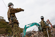 Soldiers from the Japanese Self Defense Forse (JSDF) use mechanical claws and heavy plant machinary as they take part in clean-up operations in Ishinomaki that was badly affected by the earthquake and tsunami that struck on March 11th.  Ishinomaki, Miyagi, Japan. Friday May 6th 2011