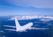 Airliner flying over snow capped mountain tops