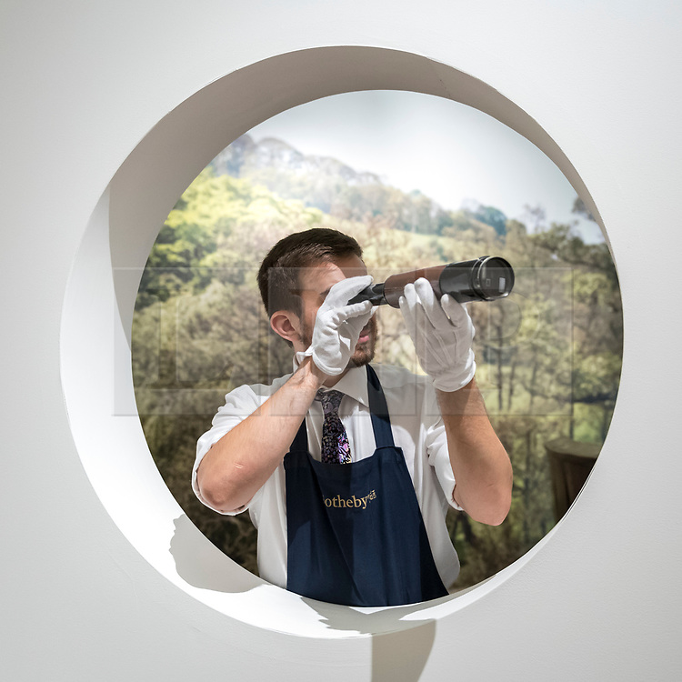 """© Licensed to London News Pictures. 26/10/2018. LONDON, UK. A staff member presents """"Edward Prince of Wales' telescope"""", (Est GBP800-1,200).   Preview of """"A Private View, property from the country home of Christopher Cone and Stanley J. Seeger"""" at Sotheby's, New Bond Street.  Over 200 extraordinary works will be auctioned in London on 30 October 2018.  Photo credit: Stephen Chung/LNP"""