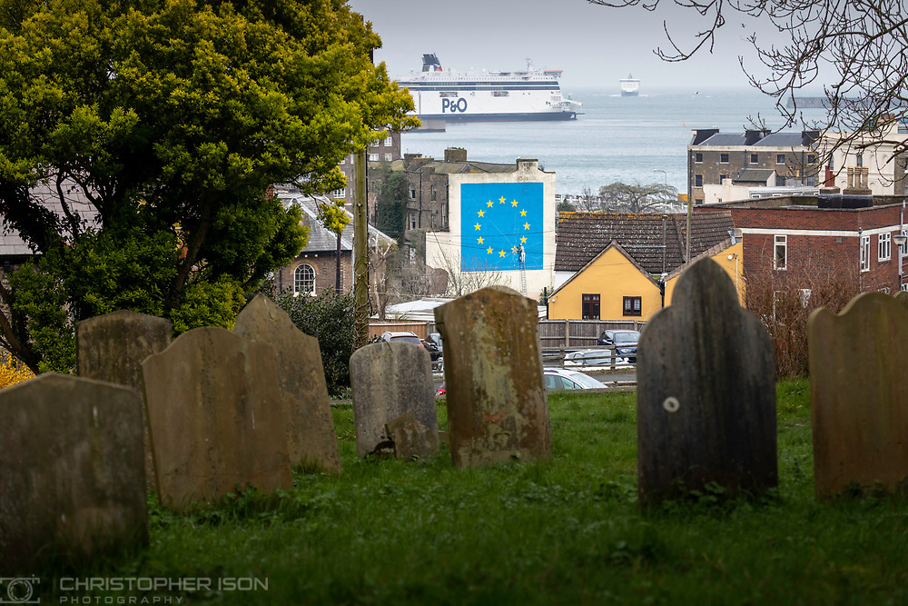 What next for Brexit??<br /> The view from a cemetery as a ferry approaches the Port of Dover where Banksy's famous Brexit mural stands large on the side of a derelict building. <br /> Prime Minister Theresa May is meeting European leaders today to ask for an extension in the hope of avoiding a no-deal Brexit. <br /> Picture date Wednesday 10th April, 2019.<br /> Picture by Christopher Ison. Contact +447544 044177 chris@christopherison.com