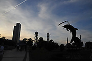 Silhouette of the Dolphin statue in Miracle Park at dusk. Alphabetic tower and the old clock tower in the background. Batumi, Georgia