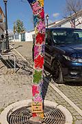 Star shaped wool crochet woollen pattern around tree trunk in street of village Mertola, Portugal