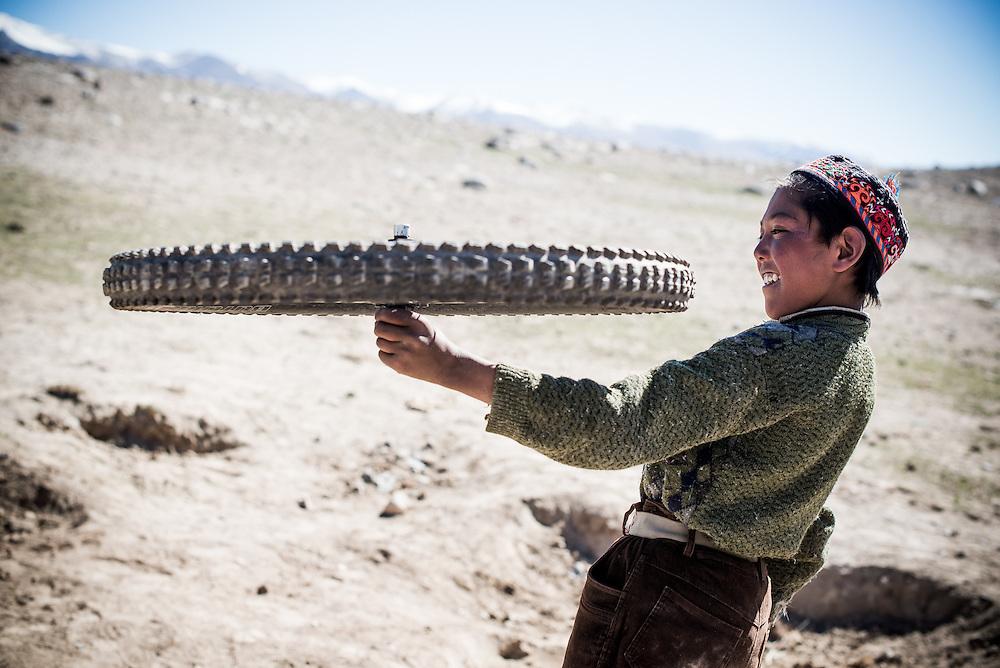 Boy with bike wheel, Wakhan Corridor, Afghanistan, 2013.