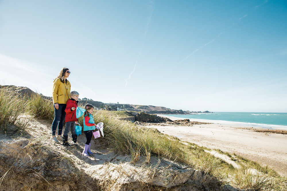 Mum and children walking through the sand dunes and taking in the views out over the beach and sea at St Ouen's Bay, Jersey, Channel Islands