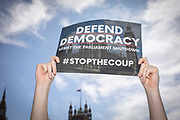 A man holds a Defend Democracy placard during the Stop The Coup protest against the proroguing of Parliament on 31st August 2019 in London in the United Kingdom. Left-wing group Momentum and the Peoples Assembly coordinated a series of Stop The Coup protests across the UK today, aimed at Boris Johnson and the UK government proroguing Parliament.