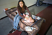 24 JANUARY 2010 -- WENDEN, AZ:  Karla Felix (CQ) changes her daughter, Belinda Beltran (CQ) 6 months, in the Red Cross shelter in Salome. Both are from Wenden. Wenden was slammed by its second 100 year flood in 10 years on Thursday night when water raced through Centennial Wash and into the small town in La Paz County west of Phoenix. Most of the town's residents were evacuated to Red Cross shelters in Salome, about 5 miles west of Wenden.    PHOTO BY JACK KURTZ