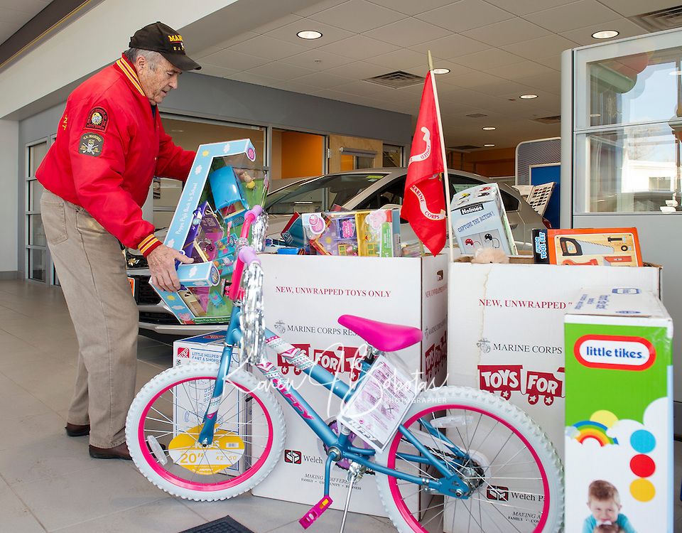 Bob Pelland collects the Marines Corps Toys for Tots from Cantin's Chevrolet on Tuesday morning.  (Karen Bobotas/for the Laconia Daily Sun)