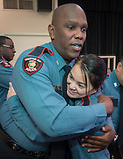 """Minhnguyet """"Nicky"""" Tran, right, gets a hug from fellow officer James Wilmore, left, following a swearing-in ceremony for new officers at the Houston ISD Police Department, March 3, 2014."""