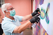 08/09/2015 - Lisbon, Portugal: António Rodrigues, 72, using a stencil to paint a fish on the wall during a Lata 65 workshop. Lata 65 was project created by Lara Seixo Rodrigues and is a creative workshop teaching street art to senior citizens. (Eduardo Leal)