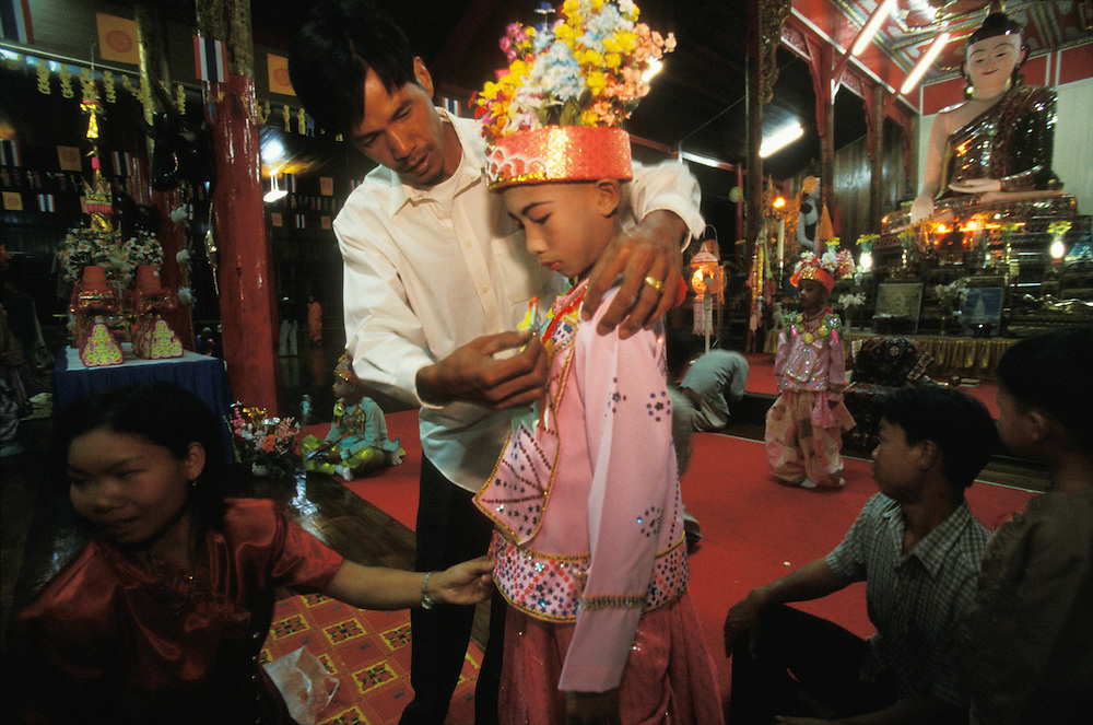 In rememberance of the Buddha, family members dress a boy in princely clothes inside a temple during Poy Sang Long, the yearly ordination of novice monks, Mae Hong Son, Thailand.