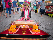 """26 JUNE 2011 - CHIANG MAI, THAILAND: A Lisu girl performs for tourists in the """"Walking Street"""" market in Chiang Mai, Thailand. The Walking Street market is a weekly, Sunday night, market along Ratchadamnoen Street in Chiang Mai. The Lisu are a Tibeto-Burman highland tribe, originally from southwest China. They can be found in China, India, Myanmar. A few drifted into North Thailand from Burma Kengtung.  PHOTO BY JACK KURTZ"""