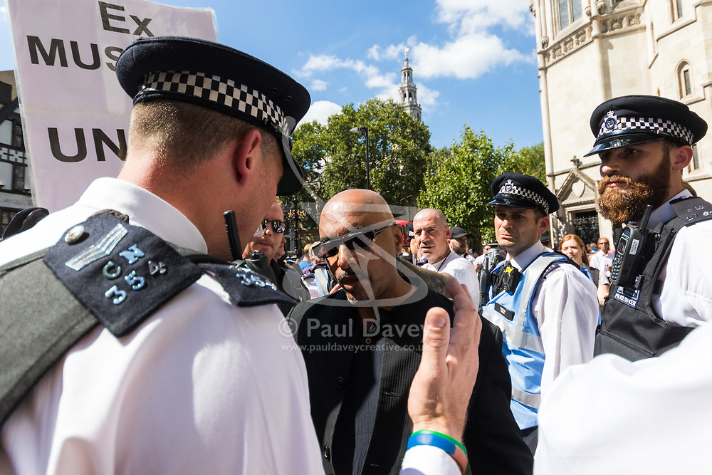 An ex-Muslim supporter of Tommy Robinson argues with police as supporters and counter protesters demonstrate outside The Royal Courts of Justice in London as an appeal by lawyers representing right wing activist Tommy Robinson win his release on bail ahead of a new hearing to be held at The Old Bailey, following his imprisonment on contempt of court charges. London, August 01 2018.