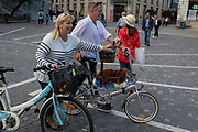 Cyclists pass through Presernov Square with their dogs in the Slovenian capital, Ljubljana, on 25th June 2018, in Ljubljana, Slovenia. Ljubljana is a small city with flat terrain and a good cycling infrastructure. It was featured at eighth on the Copenhagenize index listing the most bike-friendly cities in the world.