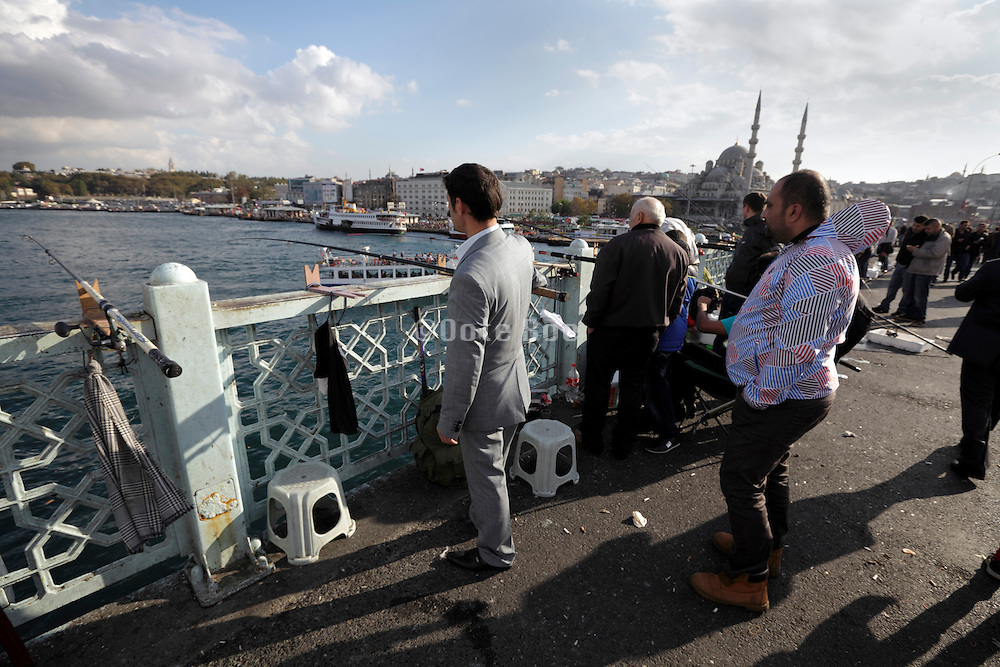 man in suit fishing on the Galata Bridge in Istanbul Turkey with the Yeni Camii in the background