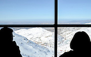 Silhouette of a man and woman looking out a window at a snowy landscape