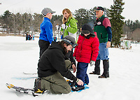 Gavin and Mrs. Hooper get advice from Bob Bolduc as they get geared up to go cross country skiing while Matt McCaslin adjusts snowshoes for William on Thursday morning at Bolduc Park as Elm Street School students experience winter Olympics sports.    (Karen Bobotas/for the Laconia Daily Sun)