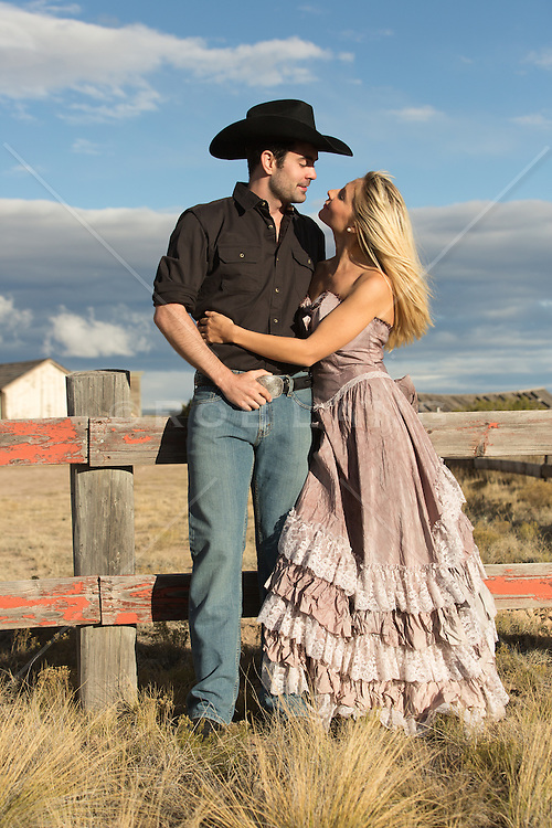 rugged cowboy with a beautiful girl in a Western style dress outdoors on a ranch