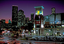 Minute Maid Park and the downtown Houston, Texas skyline with a colorful sunset sky.