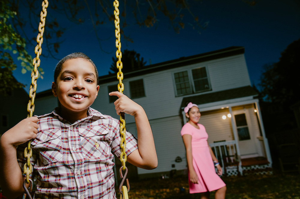 A brother and sister in their Lawrence, MA backyard photographed for the Mass Housing Annual Report.
