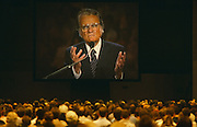 "Billy Graham preaches with sincere, confidently open hands to British Christians during Mission 89, a series of evangelical revival rallies in London, England. Graham is an Evangelical Christian who has been a spiritual adviser to several U.S. presidents including George W Bush with Time Magazine calling him "".. the nation's spiritual counselor.""  He is number seven on Gallup's list of admired people for the 20th century and member of the Southern Baptist Convention. Here he is seen towering on a giant screen over the small heads of his UK congregation who are sitting passively listening to the message of this great man of God. The scale of his personality and presence above them makes this a powerful image of leadership and of followers."