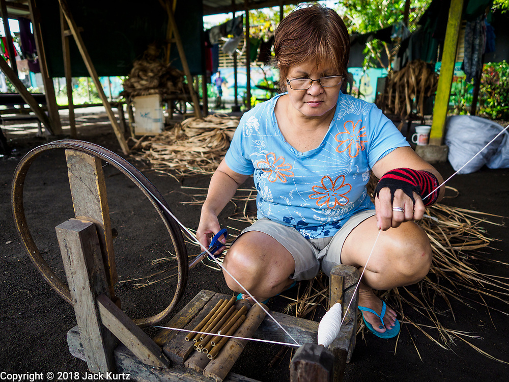 20 JANUARY 2018 - CAMALIG, ALBAY, PHILIPPINES: HILARIA SARALDE uses a spinning wheel to spin cloth she will weave into placemats and table runners to sell to tourists at the Barangay Cabangan evacuee shelter in a school in Camalig. She makes the placemats and table runners at her home and brought her supplies with her to the shelter. There are about 650 people living at the shelter. They won't be allowed to move back to their homes until officials determine that Mayon volcano is safe and not likely to erupt. More than 30,000 people have been evacuated from communities on the near the Mayon volcano in Albay province in the Philippines. Most of the evacuees are staying at school in communities outside of the evacuation zone.   PHOTO BY JACK KURTZ