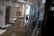 A solitary person walks alone on a wet pavement during seasonal showers on Piccadilly in the capitals West End during the third lockdown of the Coronavirus pandemic, on 22 February 2021, in London, England.