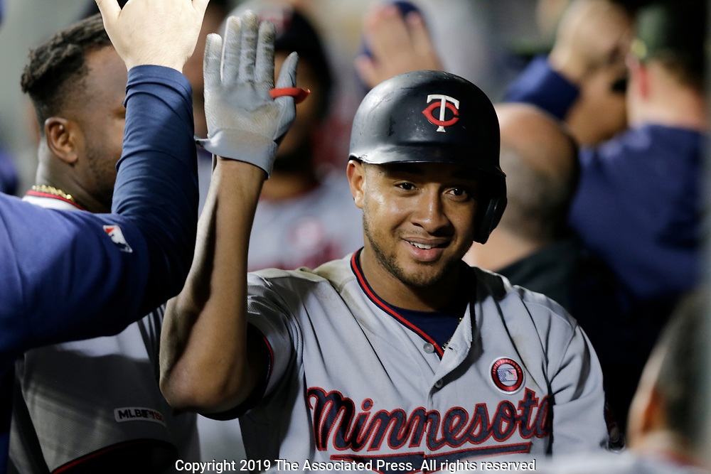 Minnesota Twins' Jonathan Schoop celebrates a home run in the dugout against the Seattle Mariners during sixth inning of a baseball game, Saturday, May 18, 2019, in Seattle. (AP Photo/John Froschauer)
