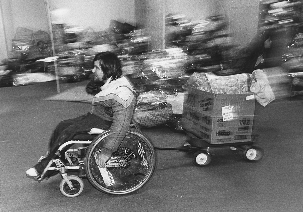 """©1982  Disabled volunteer working at """"Blue Santa"""" police toy drive in Austin"""