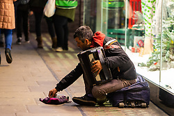 A Romanian street musician picks coins out of his hat. Homeless Britons are coming under increasing pressure as a surge of Roma beggars from Romania arrive on the streets of London to take advantage of the generosity of Christmas shoppers. London, December 04 2018.