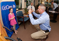 Vivian Kennell sports a big smile for Gilford Police Detective Sgt. Kris Kelley as he takes her picture to put in her Child ID booklet at the office of Children's Dentistry of the Lakes Region Thursday afternoon.  (Karen Bobotas/for the Laconia Daily Sun)Gilford Police Department and Children's Dentistry of the Lakes Region host Child ID booklet program September 15, 2011.  (Karen Bobotas/for the Laconia Daily Sun)