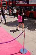 Lady shopper carrying pink bag walks past pink carpet outside an Oxford Street shop in central London.
