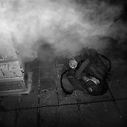 A homeless man sleeps on a grate while condensation and heat from the exhaust from a skyscrapers heating system blows past him at the corner of York Street and King Street West located in Toronto's Financial District..(Credit Image: © Louie Palu/ZUMA Press)