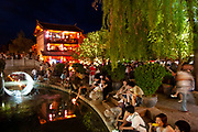Tourists gather to float flower shaped lanterns along a small waterway through the centre of Lijiang, Yunnan, China.