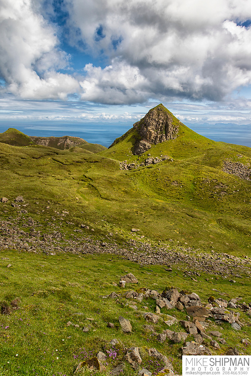 The Quiraing, Trotternish Ridge, on the Isle of Skye, looking east toward the North Atlantic Ocean. The Quiraing is an 18-mile long landslide that occurred roughly 6 million years ago when the heavy overburden of lava rock crushed the soft underlying sandstone beneath and fell toward the sea. Parts of the Quiraing are still moving slowly toward the ocean.