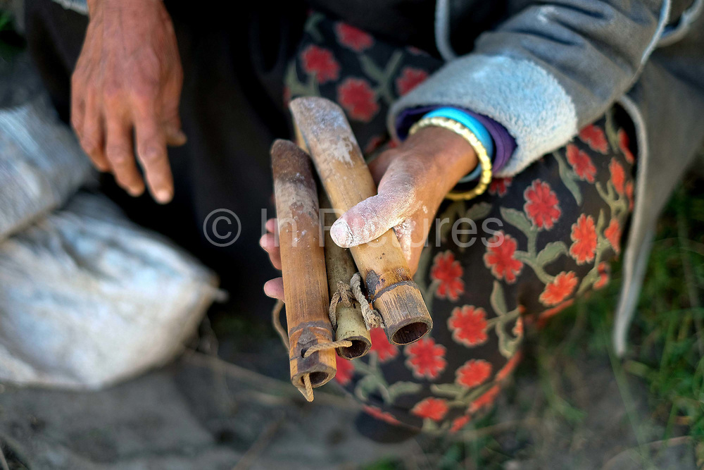 A sheep farmer holds bamboo tubes used for dosing sheep with salt which they do every day, Chubja, Bhutan. With the easy availability of commercially processed wool and other alternatives for fabric for weaving, and the lack of human resources to look after the sheep, farming of sheep has gradually been in decline in Bhutan.