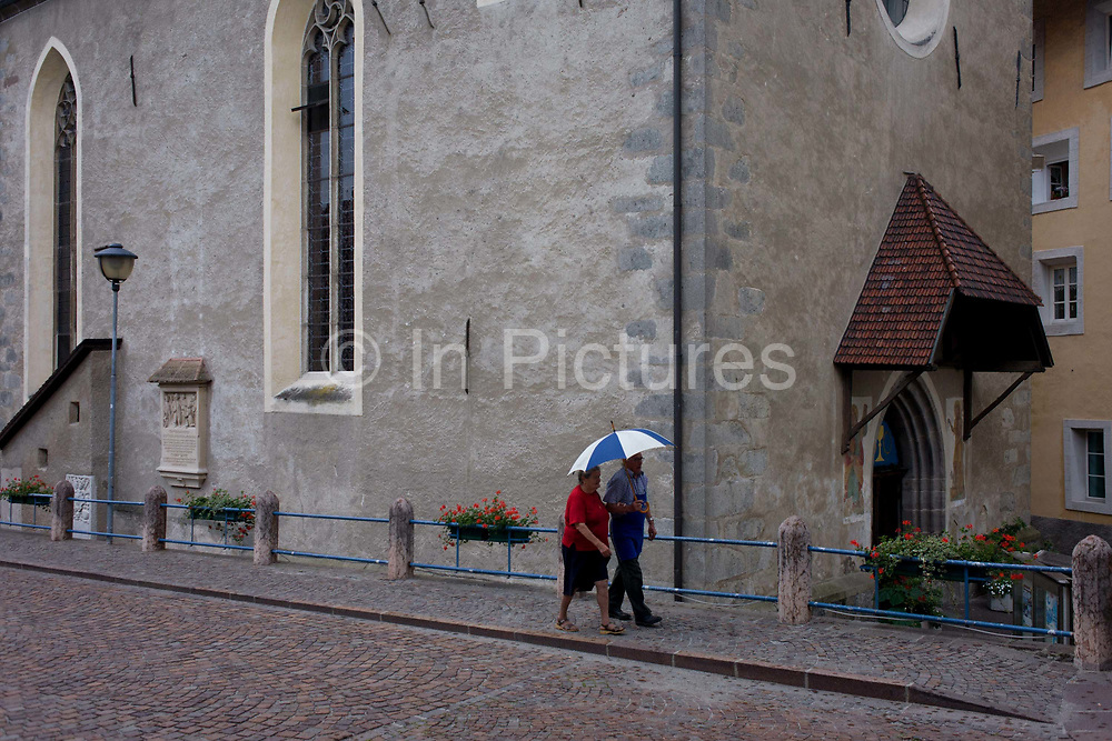 Elderly couple walk in the rain past the church in Klausen-Chiusa in the Italian south Tyrol. Using an umbrella against the summer shower, they walk towards the town centre. Klausen (Italian: Chiusa) is a commune (municipality) in South Tyrol in northern Italy, located about 20 kilometres (12 mi) northeast of the city of Bolzano. In the 2011 census, 91.3% of the population speak German, 7.9% Italian and 0.8% spoke the ancient Ladin langauge as their mother tongue.